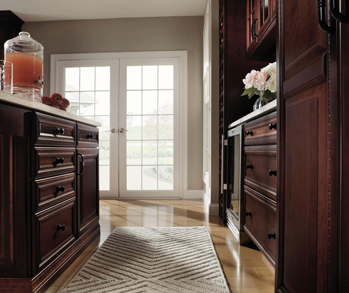 Dark cherry kitchen cabinets with glass cabinet doors by Decora Cabinetry