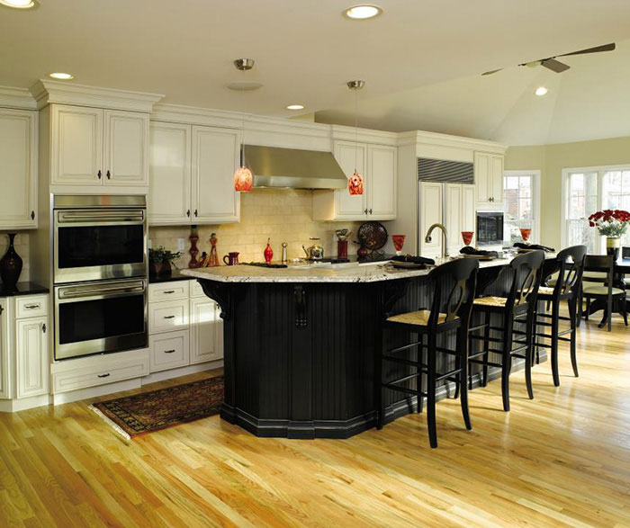 Off white cabinets with black kitchen island by Decora Cabinetry